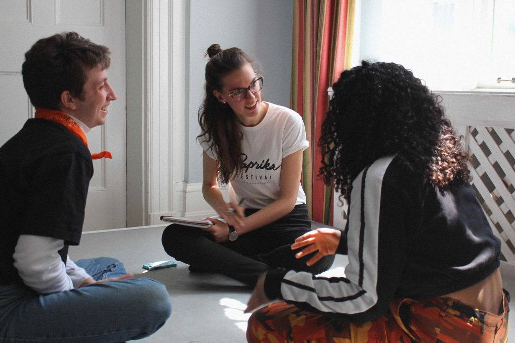 Three people sit on the floor with their legs crossed. We can see the profile of the person on the left, the full face of the person in the middle, and the person on the right has their back to us. The person on the left and the person in the middle are smiling.
